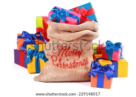 Rustic burlap Christmas gift sack with a Merry Christmas greeting on the side surrounded by colorful gift-wrapped presents over white - stock photo