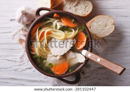 rustic chicken soup with noodles and vegetables close-up. horizontal view from above, - stock photo