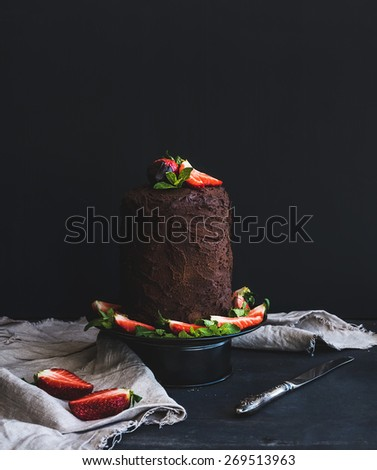 Rustic chocolate high cake with strawberry, dark background, selective focus  - stock photo