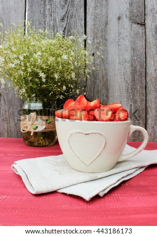Rustic composition with bowl full of sweet tasty ripe strawberry and bouquet of cute wildflowers in a glass top decorated with jute and wooden ladybirds. Vintage decor. Romantic style. Lifestyle - stock photo