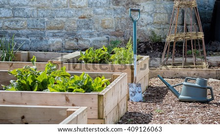 Rustic Country Vegetable & Flower Garden with Raised Beds. Spade & Watering Can - stock photo