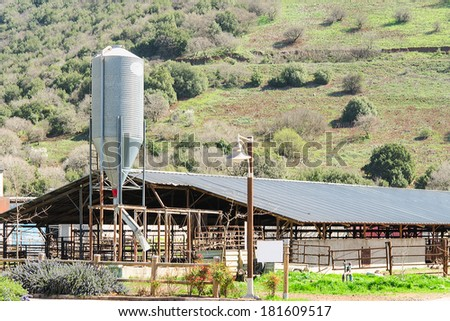 Rustic cowshed with silo in the countryside against spring blossoming hill - stock photo
