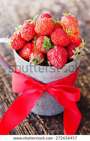 Rustic cup filled with succulent juicy fresh ripe red strawberries on wooden table - stock photo