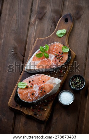 Rustic cutting board with raw salmon fillets, high angle view - stock photo