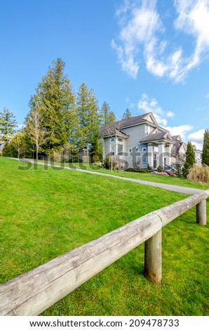 Rustic fence with a beautiful house in the background. - stock photo