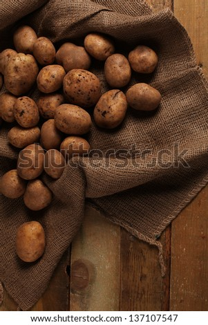 Rustic fresh unpeeled potatoes on a wooden desks - stock photo