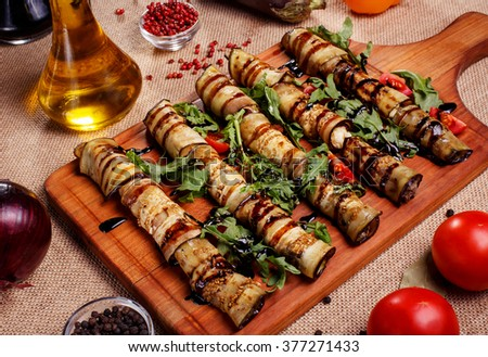 Rustic fried stuffed eggplant with cheese and meat decorated with arugula, tomatoes and sauce on a wooden board - stock photo