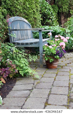 Rustic garden bench and pink geraniums - stock photo