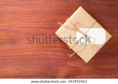 Rustic gift box packed into brown paper tied by twine with blank white card on old wooden table with space for text - stock photo