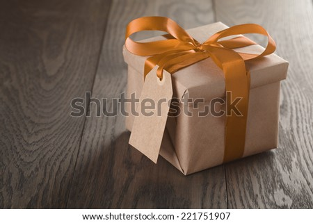 rustic gift box with orange ribbon bow and empty tag, on old wood table - stock photo
