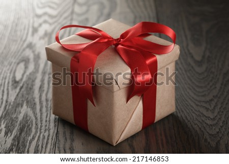 rustic gift box with red ribbon bow, on old wood table - stock photo