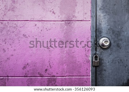 rustic grey metal door with knob and lock on dirty stain texture groove wall - stock photo