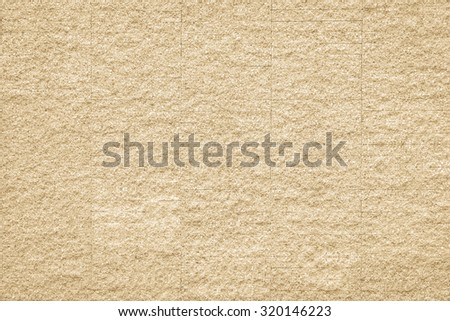 Rustic grunge granite tiled wall detailed pattern texture in natural light yellow cream color tone: Rough rock stone tile wall finishing material detail wallpaper backdrop for interior design   - stock photo