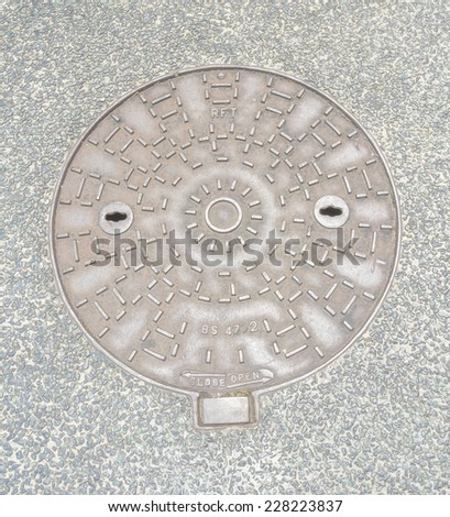 Rustic grunge storm drain manhole cover - stock photo