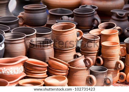 Rustic handmade ceramic clay brown terracotta cups souvenirs at street handicraft market - stock photo