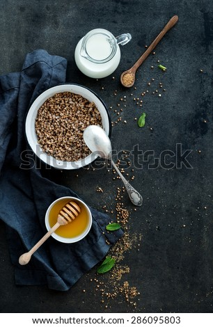 Rustic healthy breakfast set. Cooked buckwheat groats with milk and honey on dark grunge backdrop. Top view, copy space - stock photo