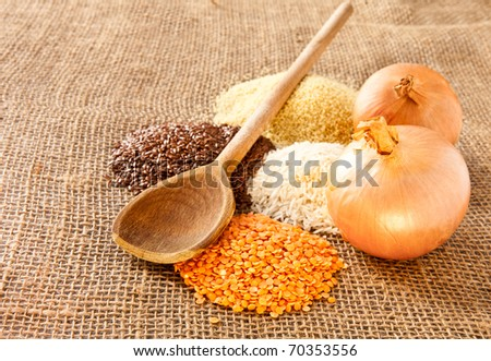 Rustic image of a mixture of grains, onions and a wooden spoon - stock photo