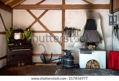 Rustic interior in an old forge with a wood burning oven, old piano, tools hanging on the wall and old metal anvil - stock photo