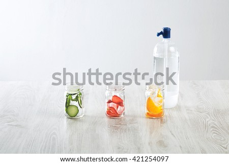 Rustic jars with ice and various fillings: orange,strawberry,cucumber and mint prepared to make fresh homemade lemonade with sparkling water from siphon Healthy beverage to cool down in summer time - stock photo