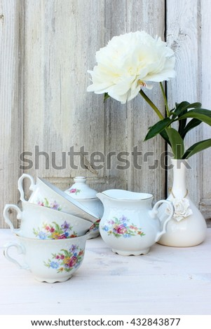 Rustic kitchen setting with fine porcelain dinner ware set decorated with floral pattern and white porcelain vase with single flower of peony. Vintage style of decor in an aged white color - stock photo