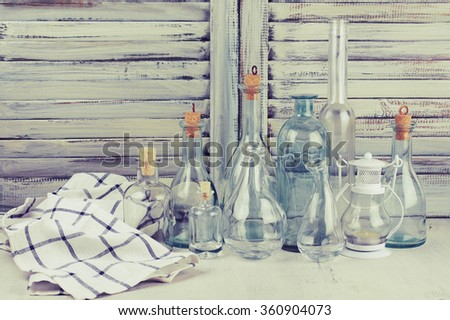 Rustic kitchen still life: empty glass bottles, lantern and towel against vintage wooden shutters. Filtered toned image. - stock photo