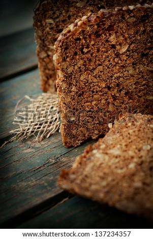 Rustic loaf of bread with sunflower seeds on wood background - stock photo