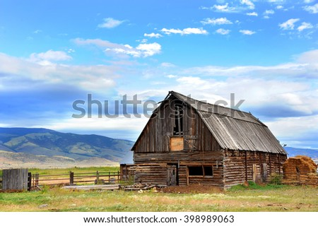 Rustic log barn has wooden roof and is in disrepair.  Field behind barn rolls across the distance to the mountains of Paradise Valley, Wyoming. - stock photo