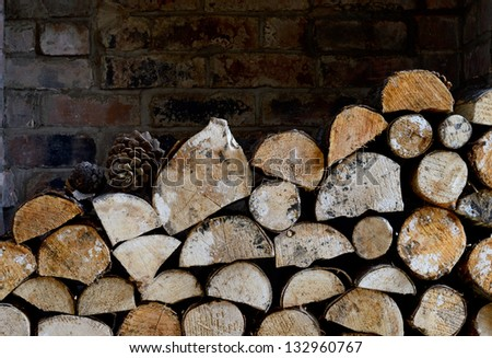 Rustic logs stacked in a holiday cottage open fire place in natural winter light. Copy space. - stock photo