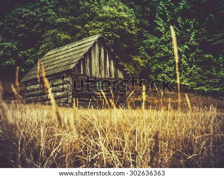 Rustic Old Farm Building Or Barn In A Field Of Grass - stock photo