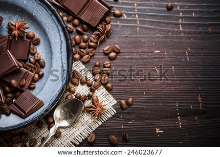 Rustic old plate with silver teaspoon, coffee beans and chocolate  - stock photo
