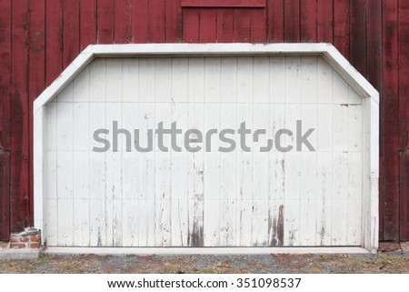 Rustic old red and white barn door with peeling paint - stock photo