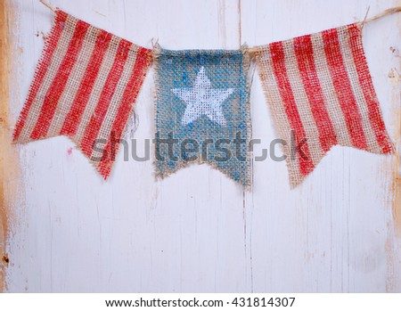 Rustic patriotic banner of three painted burlap flags on white washed wooden background. Center is white star on blue. Outside is red and white stripes for Flag day, July 4th and other USA holidays  - stock photo