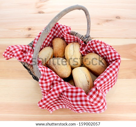 Rustic picnic basket of fresh bread rolls on a pine table - stock photo
