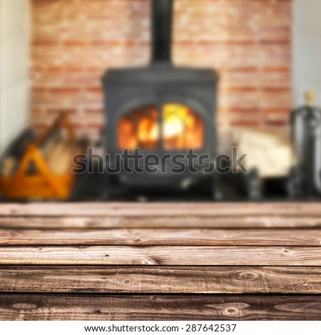 Rustic planks, wood burning stove in the background - stock photo