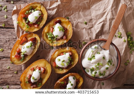 Rustic potato skins with cheese, bacon and sour cream close-up on the table. Horizontal view from above - stock photo