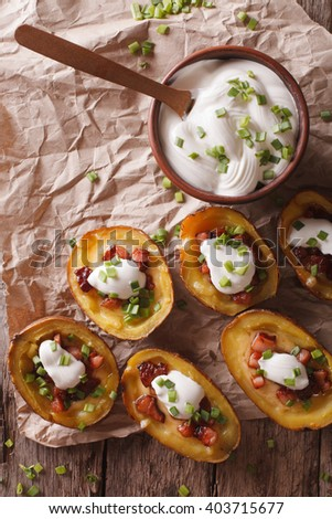 Rustic potato skins with cheese, bacon and sour cream close-up on the table. vertical view from above - stock photo