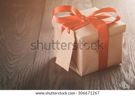 rustic present box with red ribbon on wood table, vintage toned photo - stock photo
