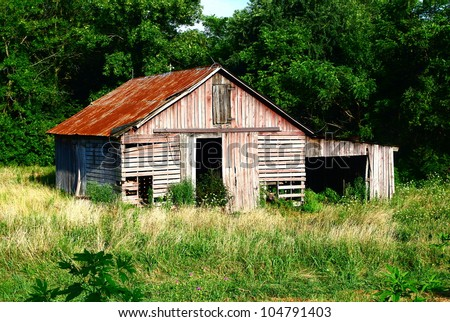Rustic Red & Gray Slatted Barn:  Weathered red tin roofed & faded red & lite gray slatted barn in country field with wildflowers and weather vane - stock photo