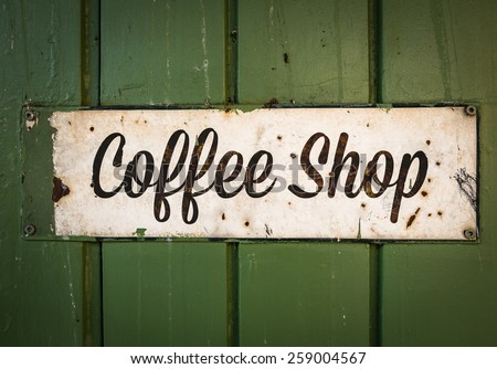 Rustic Retro Coffee Shop Sign On A Green Wooden Storefront - stock photo