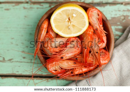 Rustic serving of cooked shrimp in a pottery bowl with lemon on a grungy painted wooden table top - stock photo