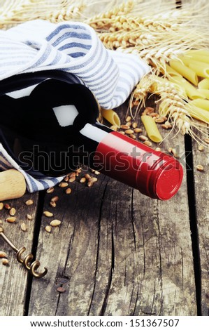Rustic setting with bottle of red wine and pasta  - stock photo