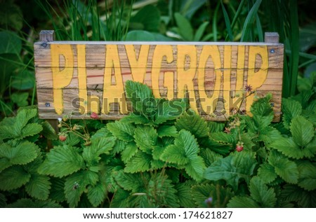 Rustic Sign In The Garden Of A Rural School Playgroup - stock photo