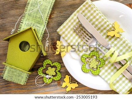 Rustic spring festive table setting with plate, napkin and tableware - stock photo