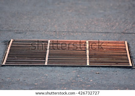 rustic square manhole drain cover in the street,Steel cover drain water sun reflections. - stock photo
