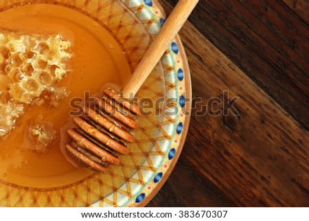 Rustic still-life of golden honeycombs with fresh honey and drizzler on decorative plate over dark wood background.  Top view. Closeup with selective focus and copy space. - stock photo
