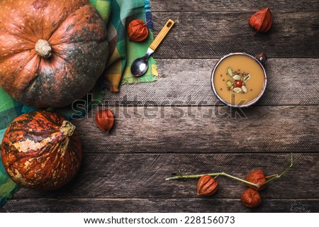 Rustic style Pumpkins and soup with seeds and ground cherry on wooden table. Autumn Season food photo - stock photo