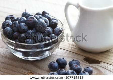 Rustic table setting of blueberries and a small white milk pitcher - stock photo