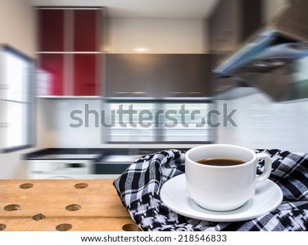 Rustic tabletop with coffee cup over modern kitchen blurry background - stock photo