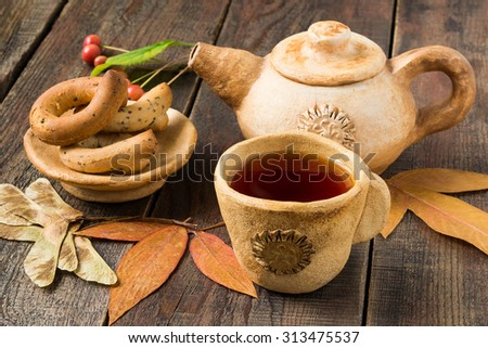 Rustic Tea Party: hot tea in earthenware teapot and cup, autumn leaves and fruits on a wooden table. Selective focus - stock photo