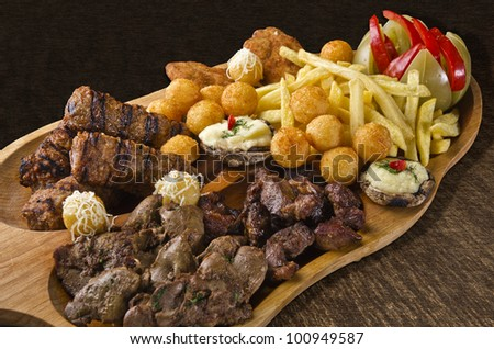 Rustic tray with various meats, cheese balls, french fries and assorted vegetables - isolated - stock photo
